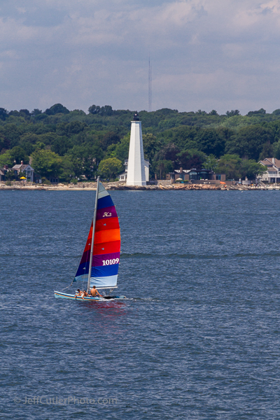 A sailboat goes in front of New London Harbor Light.